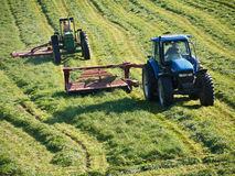 Farmers Cutting Hay with Tractors stock images