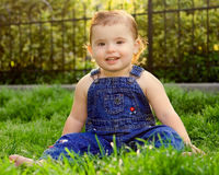 Farmers Daughter. A beautiful baby girl sitting in the grass in overalls stock photo
