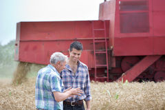 Farmers on field with combine harbester Royalty Free Stock Images