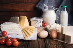 Farmers food products: milk, cream, cheese, eggs, cottage, butter. Rustic composition. Organic food concept. Farmers food products: milk, cream, cheese, eggs Stock Photo