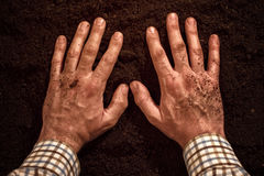 Farmers hands on fertile soil ground Royalty Free Stock Images