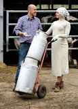 Farmers holding large metallic milk cans. Cheerful male and female farmers holding large metallic milk cans in hangar with cows Stock Photo