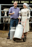 Farmers holding large metallic milk cans. Smiling male and female farmers holding large metallic milk cans in hangar with cows Stock Photo