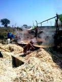 Farmers making brown sugar (jaggery) in rural india. Farmers boiling juice of sugar cane to make brown sugar, also called as jaggery, in rural area of ashoknagar Stock Photo
