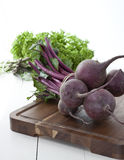 Farmers market beetroot. Fresh beetroots from farmers market on dark wooden board with green lettuce and asparagus on background royalty free stock photography