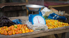 Farmers Market Fresh tomatoes. A farmer's market vegetable stall selling fresh tomatoes, with a weighing scale in the middle. Photo taken on: January 12th, 2013 Stock Images