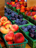 Farmers market fruit. Plums, peaches in green plastic containers at farmers market Royalty Free Stock Images