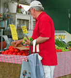 At the Farmers Market. A photograph of a man selecting green peppers at the farmers market Stock Photos