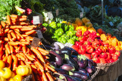 Farmers Market Produce Stand. Portland, Oregon, South Park Blocks Farmers Market produce of red,yellow and green Bell Peppers, eggplant,chard,carrots and Royalty Free Stock Photo