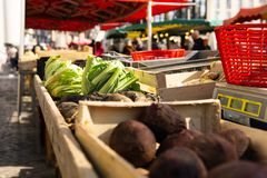 Farmers market scene in France vegetables and scales. Market scene greens and root vegetables sitting on tables with scales and baskets farmers market france stock photos