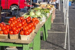 Farmers Market Table 4. Tomatoes and a variety of vegetables in baskets aranged on tables at a farmers market Stock Photos