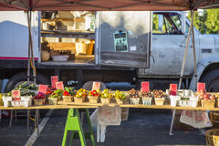 Farmers Market Table 7. Variety of fruit and vegetables in baskets aranged on tables with a white truck in the background at a farmers market Stock Photos