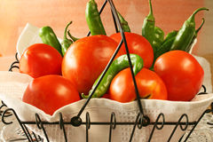 Farmers Market Tomatoes and Peppers. Tomatoes and peppers in wire basket purchased at a local farmers market Royalty Free Stock Images