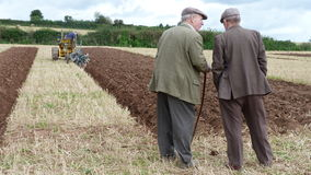 Farmers at a ploughing match in England UK. Two farmers discuss the merits of a furrow Stock Photo