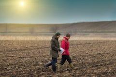 Farmers on plowed field Royalty Free Stock Photo