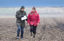 Farmers on plowed field Stock Image