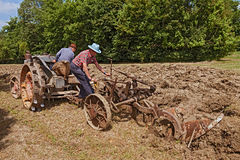 Farmers plowing with an old tractor Royalty Free Stock Photography