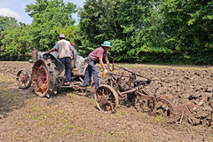 Farmers plowing with an old tractor Royalty Free Stock Photos