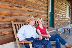 Farmers Sitting Outside of Cabin - horizontal Stock Image