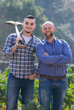 Farmers with spades at plantation. Two male farmers standing with spades at plantation Stock Photo