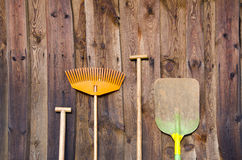 Farmers tools on old barn wall background Stock Photos