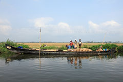 Farmers transport the gunny bags containing the harvested rice in a wooden boat Stock Image