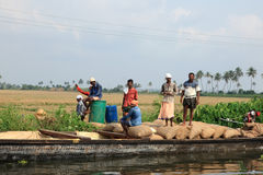 Farmers transport the gunny bags containing the harvested rice in a wooden boat Royalty Free Stock Images
