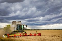 Harvesting under a threatening sky. Farmers trying to beat the weather while harvesting under a stormy looking sky which is threatening rain stock photography