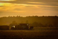 Farmers working on a sunset Stock Photography