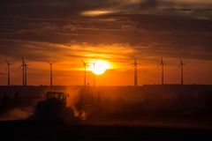 Farmers working with a tractor on the field at sunset with wind turbines in the background Royalty Free Stock Photography