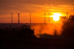 Farmers working with a tractor on the field at sunset with wind turbines in the background Royalty Free Stock Photos