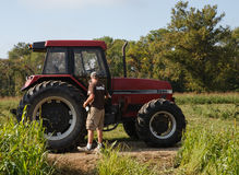 Farmhand Cleaning Tractor Royalty Free Stock Photo