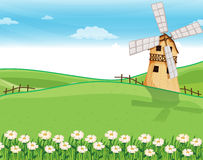 A farmhouse above the hills with a windmill Royalty Free Stock Photos