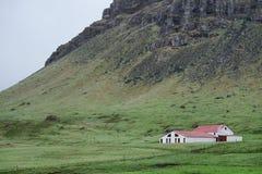 Farmhouse at base of mountains, Iceland Stock Photos