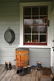Farmhouse, building. Boots at back porch part of the building, home related Stock Photo