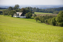 Farmhouse in green fields Royalty Free Stock Image