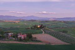 Farmhouse, green hills,cypress trees in Tuscany at sunset Stock Photo
