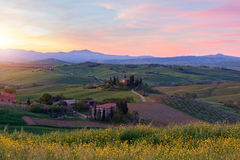 Farmhouse, green hills,cypress trees in Tuscany at sunset Royalty Free Stock Photography