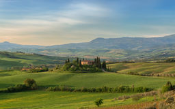 Farmhouse, green hills,cypress trees in Tuscany at sunset Stock Image