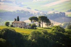 Farmhouse in Italian countryside. Farm house in the hills of the Italian countryside with field of sunflowers Stock Photos