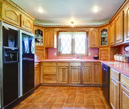 Farmhouse kitchen room with wood cabinets and pink backsplash Stock Photography