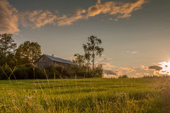 Farmhouse. In the meadows during sunset Stock Photos