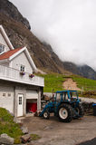 The farmhouse at the mountains. The vertical picture of the farmhouse and tractor at mountains at cloudy day stock photos