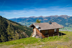Farmhouse in the mountains. Wooden farmhouse in the mountains under the blue sky stock photo