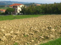 Farmhouse with ploughed field. Italian farmhouse with a yellow ploughed field in front Stock Photography