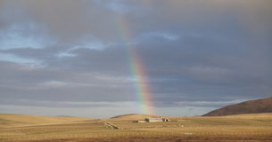 Farmhouse and rainbow. Picturesque panorama of a distant farmhouse in a field royalty free stock image