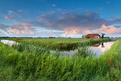 Farmhouse by river at sunset Royalty Free Stock Photos