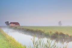 Farmhouse on riverside in morning fog Stock Photo
