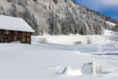 Farmhouse in snow covered mountains Royalty Free Stock Images