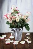 Farmhouse Style Bouquet. Beautiful bouquet of  red and white roses with baby`s breath in a metal farmhouse style vase surrounded by fallen petals Stock Photos